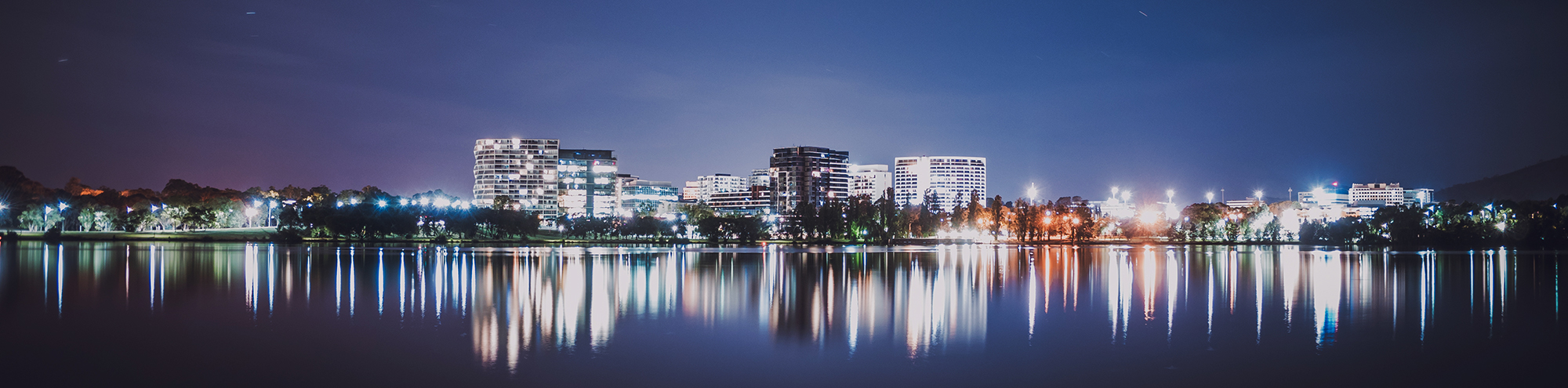 Image of the Canberra skyline at night with city lights reflecting off Lake Burley Griffin